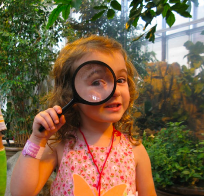 girl holding magnifying glass up to her eye
