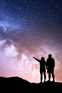 couple pointing at night sky